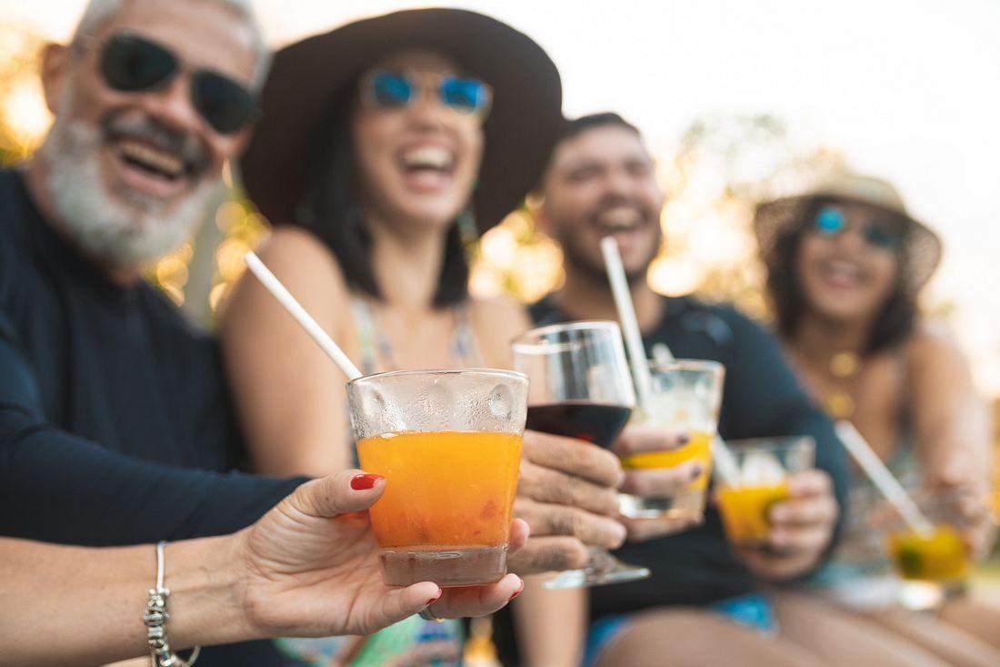 Party People trinken Alkohol durch Strohhalm