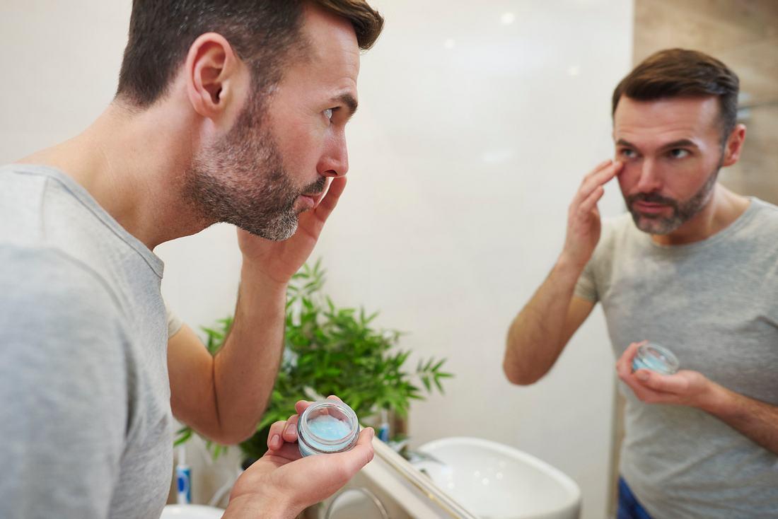 Mann benutzt Anti-Falten-Creme im Badezimmer