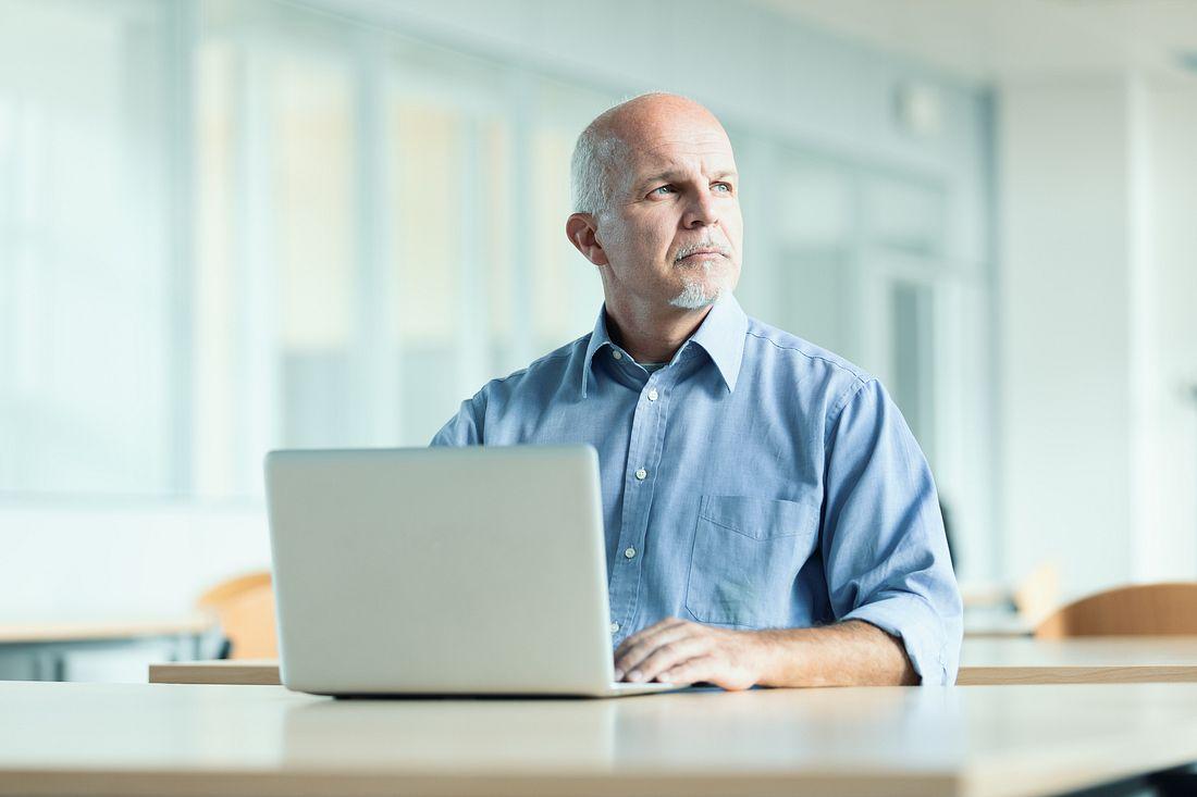 Mann mit Glatze vor Laptop