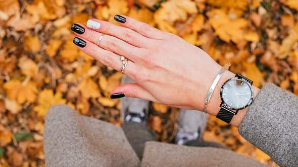 Frauenhand mit einem silbernen Armband mit Gravur und schwarzer Armbanduhr um das Handgelenk - Foto: I-Stock/Christina Vartanova