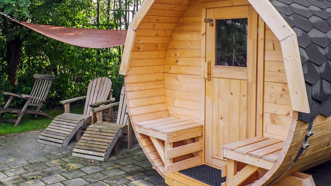 Eine runde Außensauna steht im Garten - Foto: iStock/TomekD76