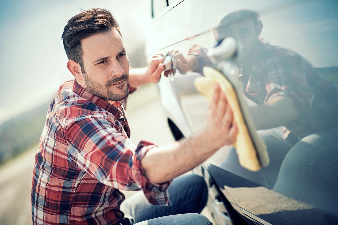 Ein Mann reinigt sein Fahrzeug mit Autopolitur