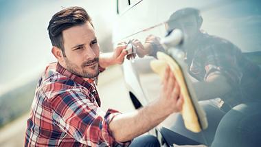 Ein Mann reinigt sein Fahrzeug mit Autopolitur - Foto: iStock/Ivanko_Brnjakovic