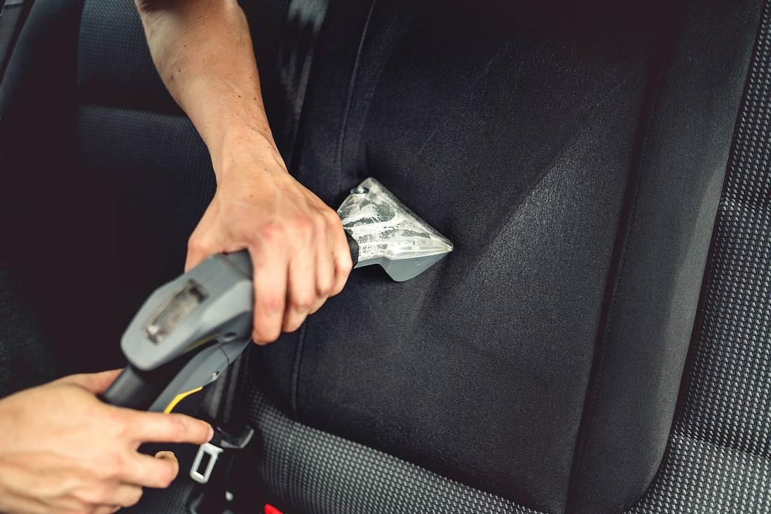 Ein Mann reinigt mit einem Autostaubsauger die Sitze