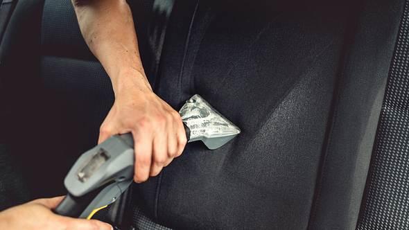 Ein Mann reinigt mit einem Autostaubsauger die Sitze - Foto: iStock/Bogdanhoda