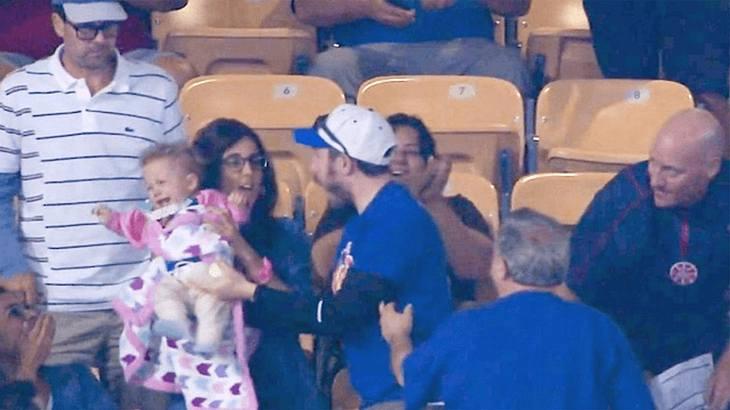 Mets vs. Dodgers: Ein Baseball-Fan versucht den Ball mit seinem Baby auf dem Arm zu fangen