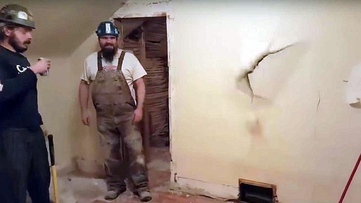 Ein betrunkener Bauarbeiter springt auf einer Baustelle durch eine Wand