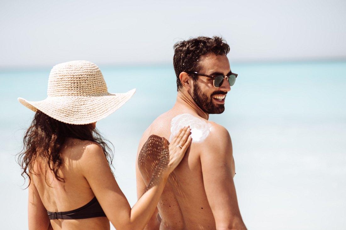 Frau cremt Rücken von Mann mit Sonnencreme ein