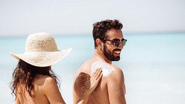 Frau cremt Rücken von Mann mit Sonnencreme ein - Foto: iStock/franckreporter