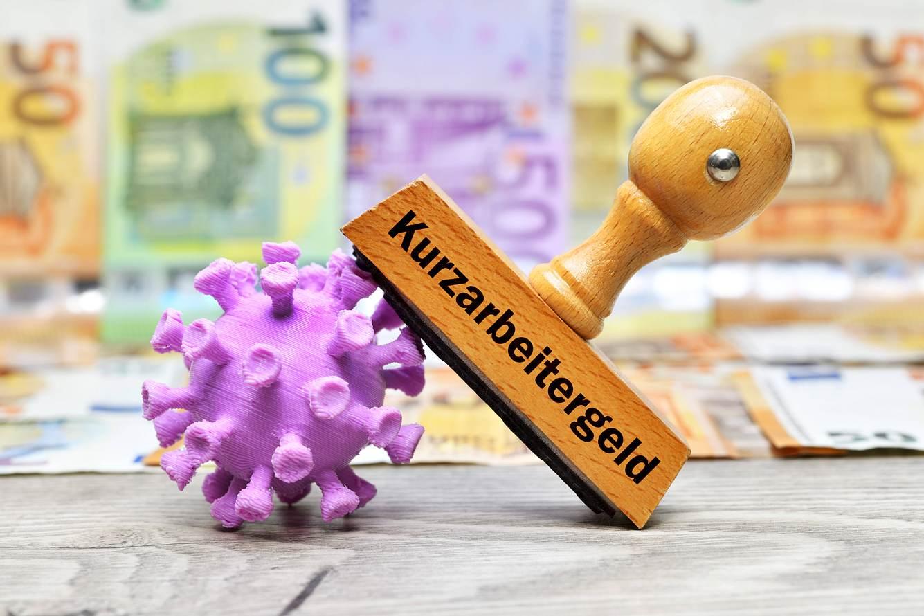 Stempel Kurzarbeitergeld, angelehnt an ein Coronavirus, im Hintergrund Tapete aus Geldscheinen