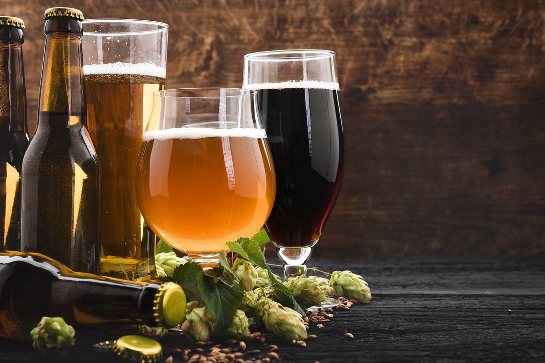 Verschiedene Biergläser und Bierflaschen auf einem Holzuntergrund