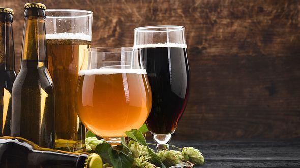 Verschiedene Biergläser und Bierflaschen auf einem Holzboden - Foto: iStock/Rouzes