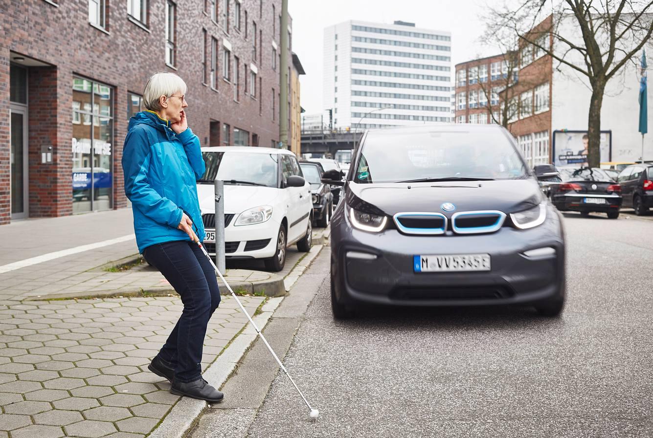 Blinde Frau überquert Straße, auf der ein BMW i3 fährt