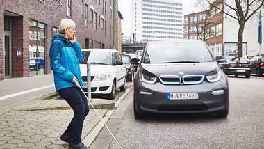 Blinde Frau überquert Straße, auf der ein BMW i3 fährt - Foto: DBSV/Schwering