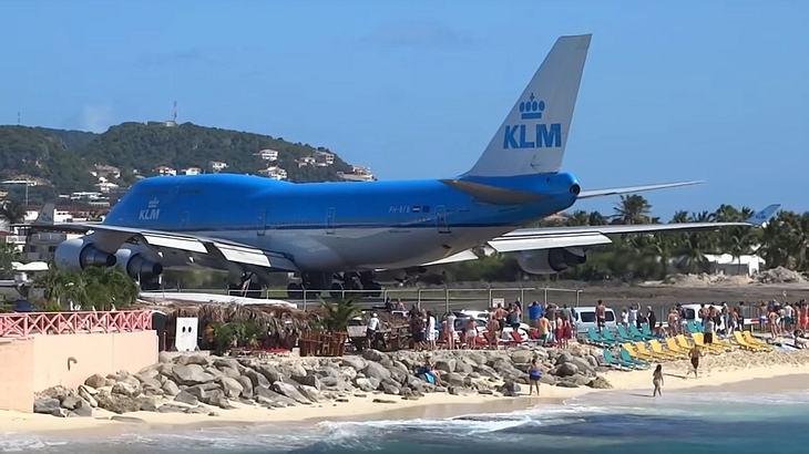 Eine KLM 747 pustet mit ihrem Triebwerk Touristen vom Strand