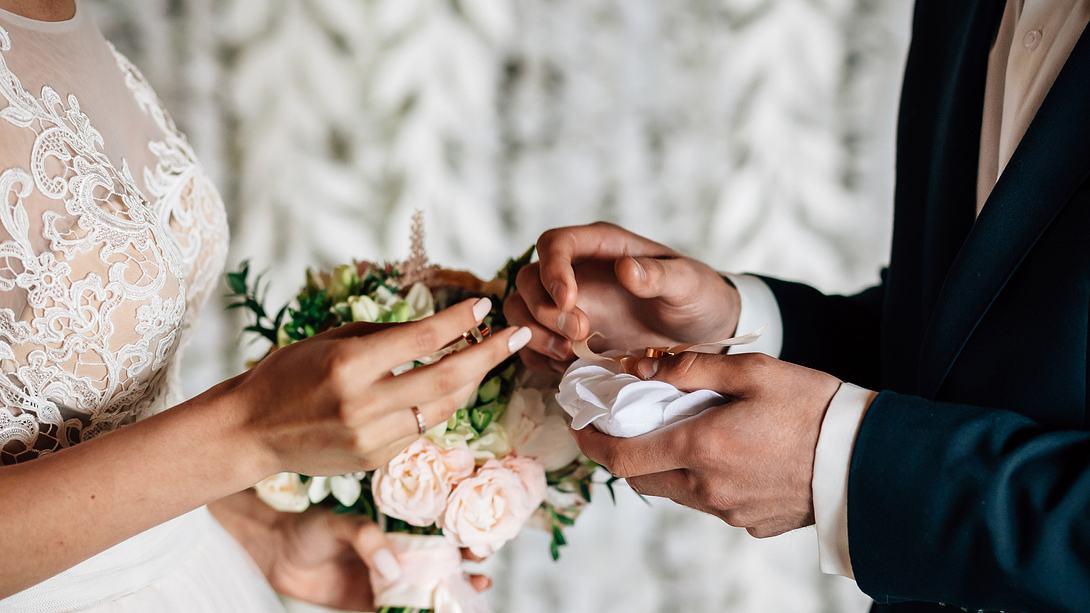 Mann und Frau tauschen Eheringe - Foto: iStock/Виктор Высоцкий