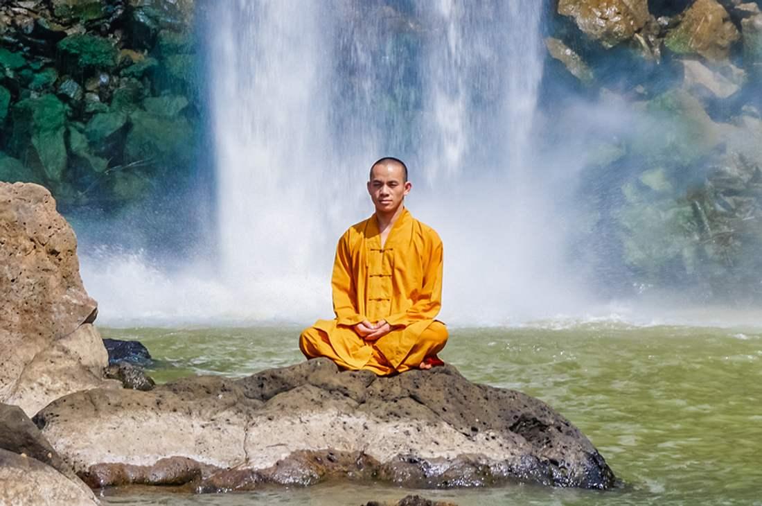 Buddhistischer Mönch meditiert auf einem Stein vor einem Wasserfall