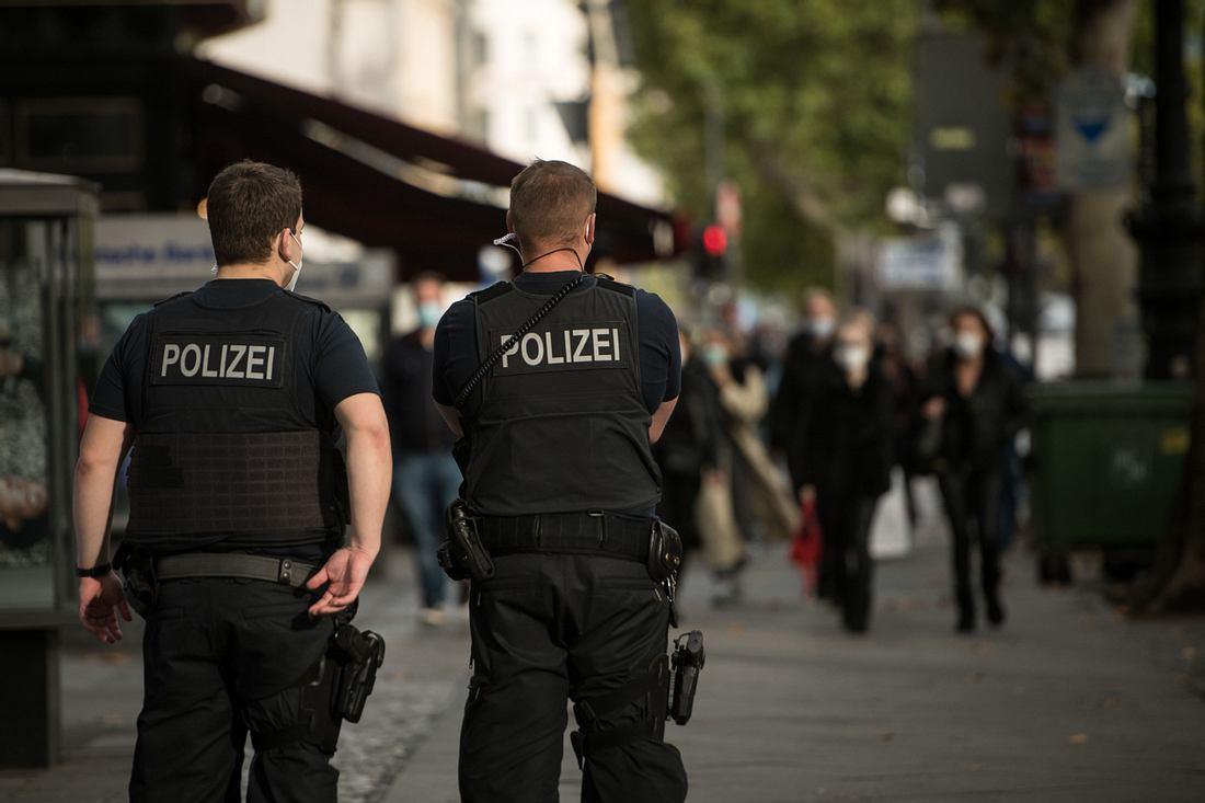 Zwei Polizisten kontrollieren Passanten auf der Straße