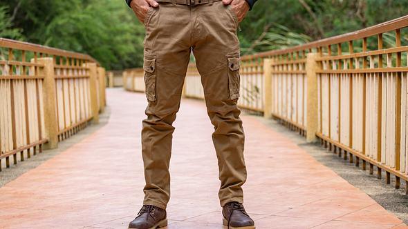 Mann trägt eine braune Cargohose auf einer Brücke im Wald - Foto: i-Stock/KCHANDE