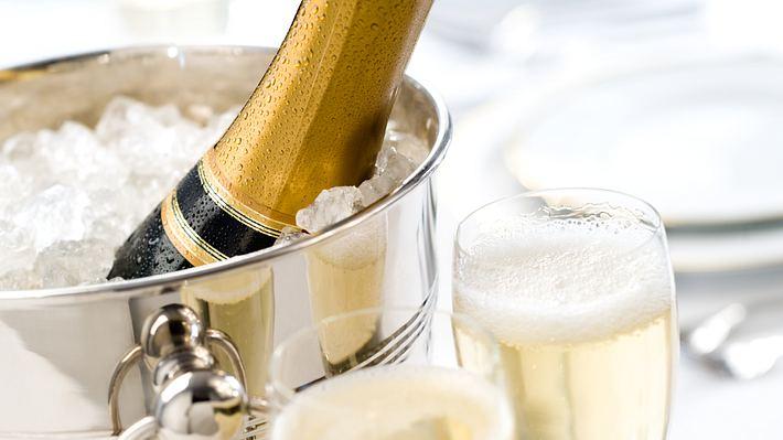 silberner Champagnerkühler mit Crush-Eis gefüllt, Champagnerflasche und zwei gefüllte Gläser zum Anstoßen - Foto: Istock/MarkSwallow