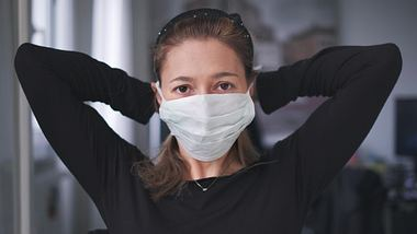Frau mit Mundschutz - Foto: iStock / LucaLorenzelli
