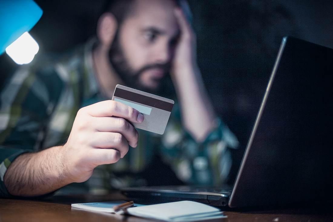 Mann mit Bankkarte am Tisch vor seinem Laptop