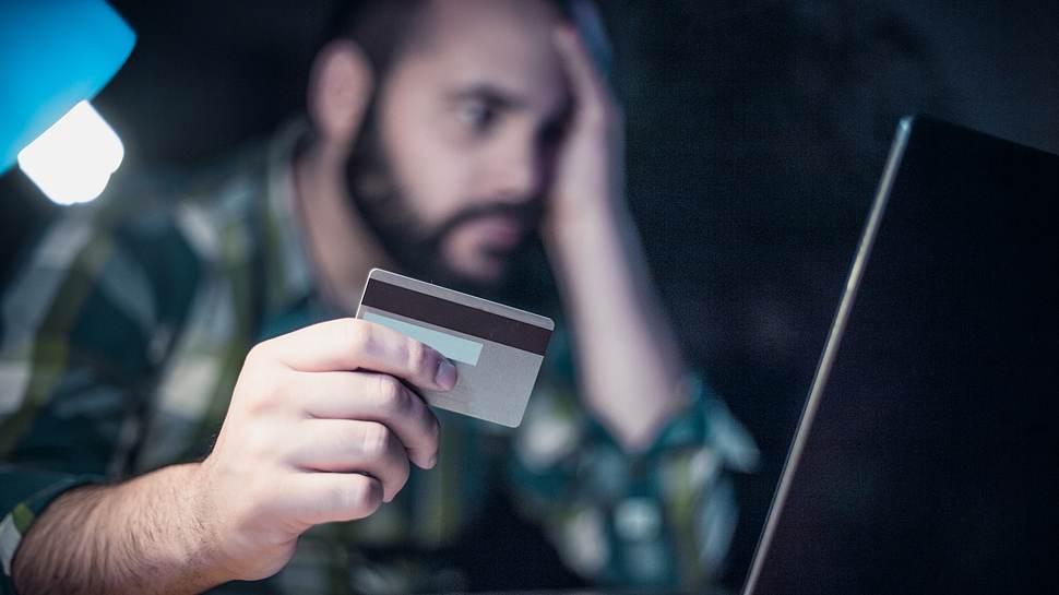 Mann mit Bankkarte am Tisch vor seinem Laptop - Foto: iStock/domoyega