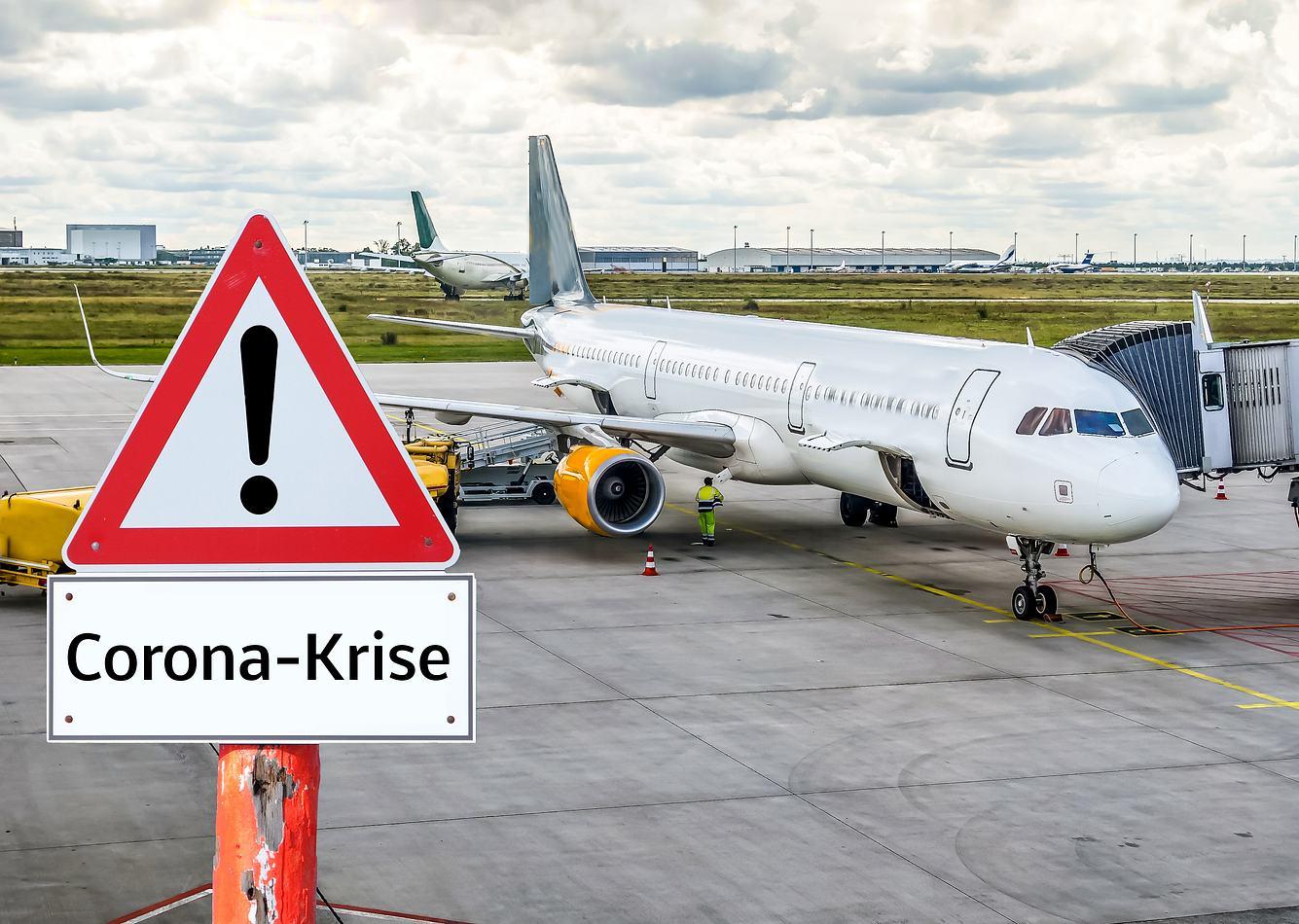 Flughafen mit Flugzeug und Corona-Warnhinweis