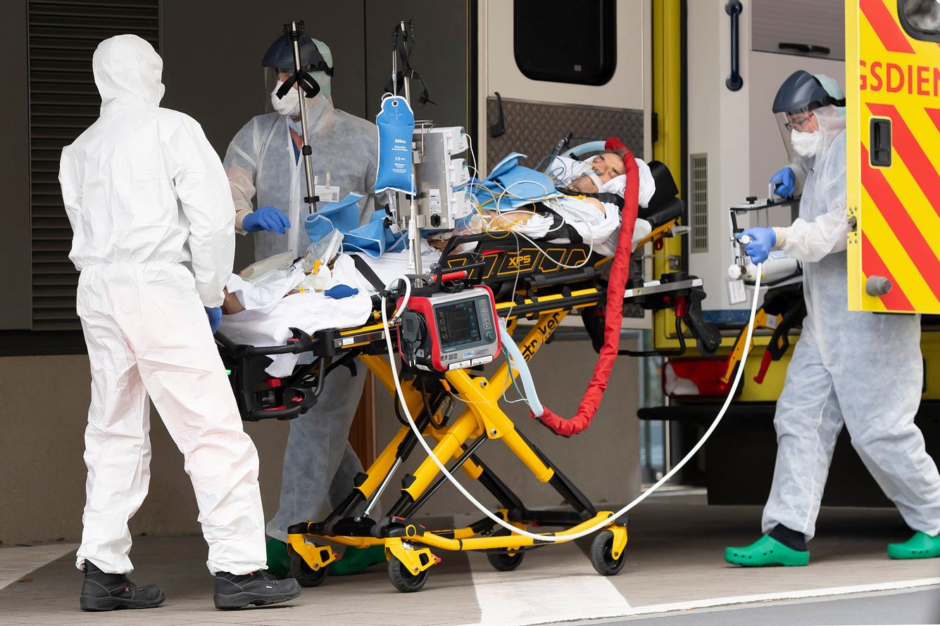 Corona-Patient wird auf einer Trage ins Krankenhaus gebracht