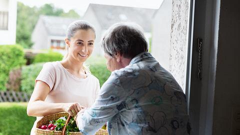 Junge Frau überreicht älterer Frau einen Einkaufskorb - Foto: iStock / SilviaJansen