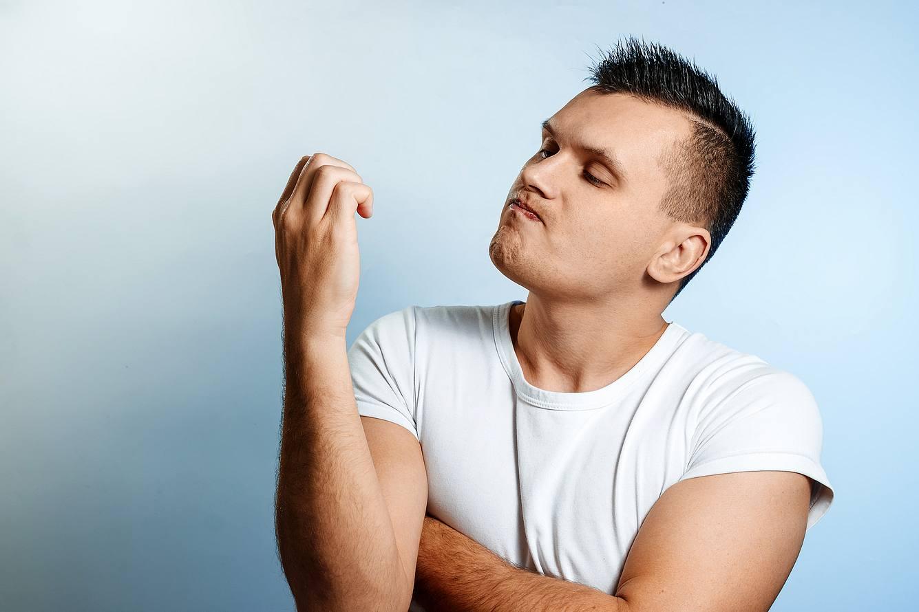 Mann betrachtet seine Fingernägel