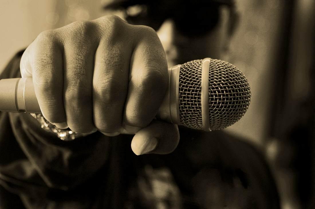 Rapper hält Mikrofon in die Kamera