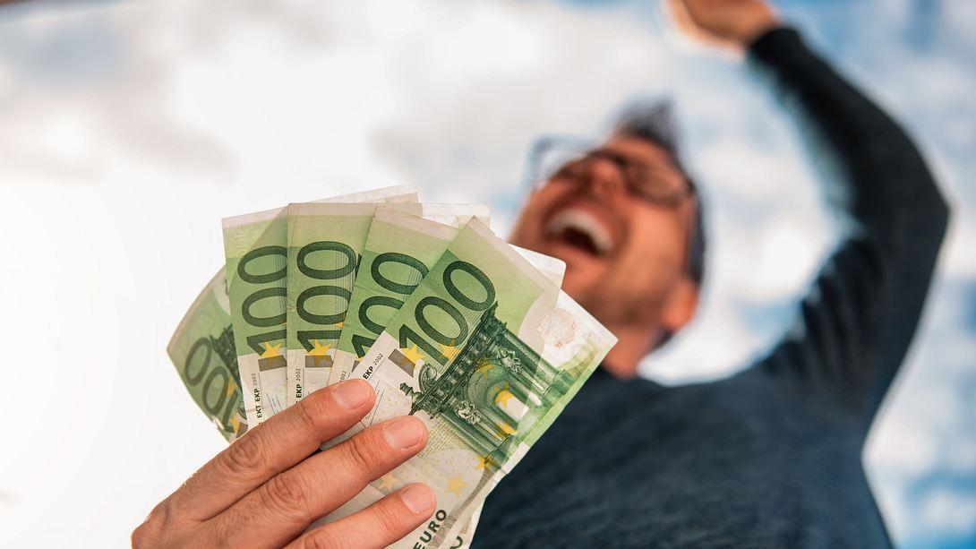 Glücklicher Mann mit fünf 100-Euro-Scheinen in der Hand - Foto: iStock / Kerkez