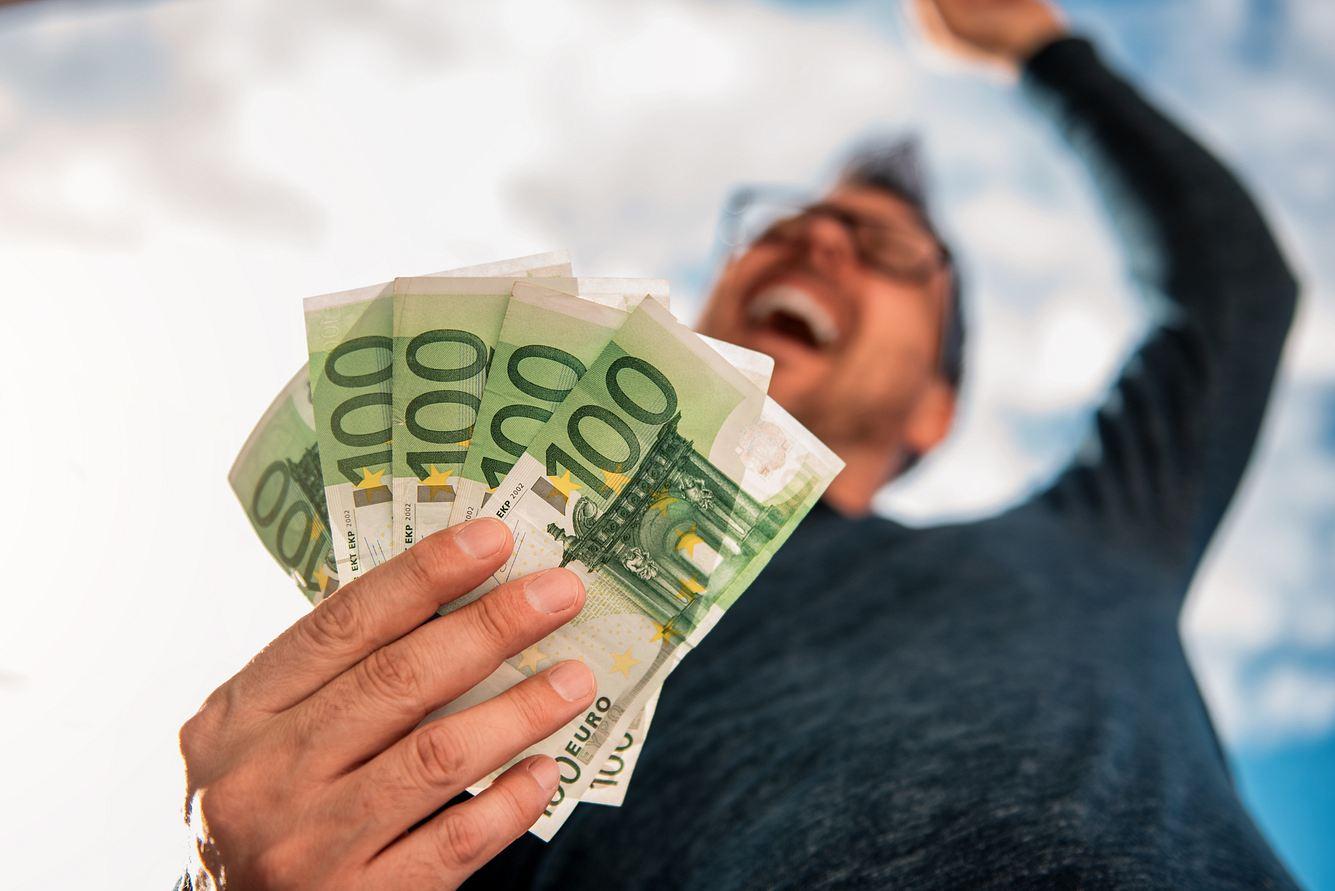 Glücklicher Mann mit fünf 100-Euro-Scheinen in der Hand