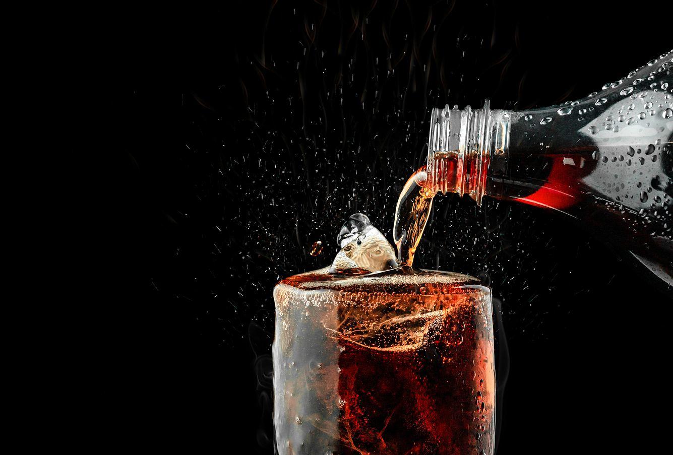 Cola, die in ein Glas gegossen wird