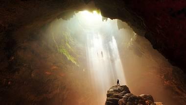 Mensch steht auf einem Felsvorsprung in einer Höhle - Foto: iStock / BudiNarendra