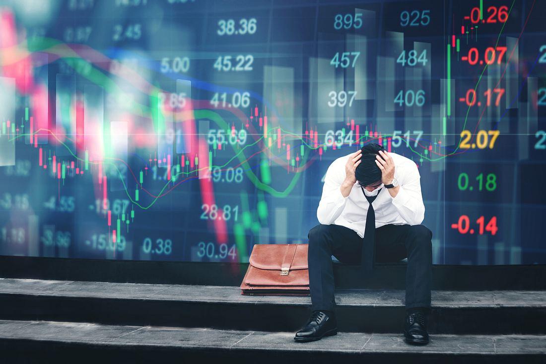 Mann sitzt vor Display mit Börsenkursen und schlägt die Hände über dem Kopf zusammen