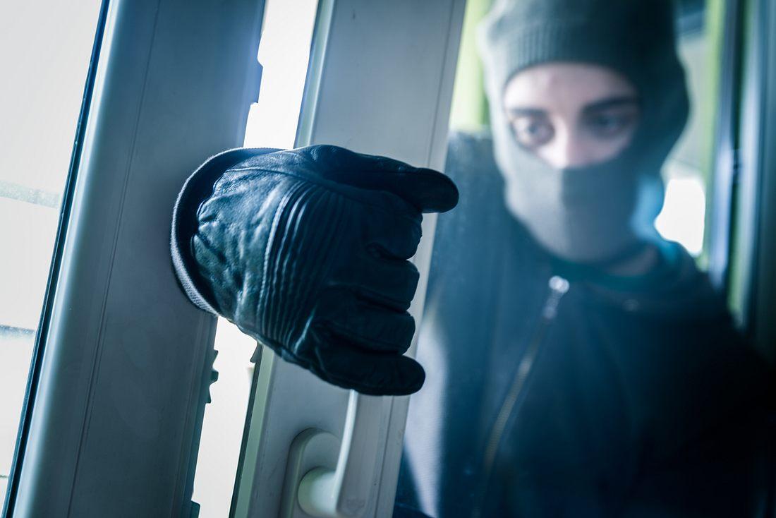 maskierter Einbrecher versucht, ein Fenster aufzubrechen