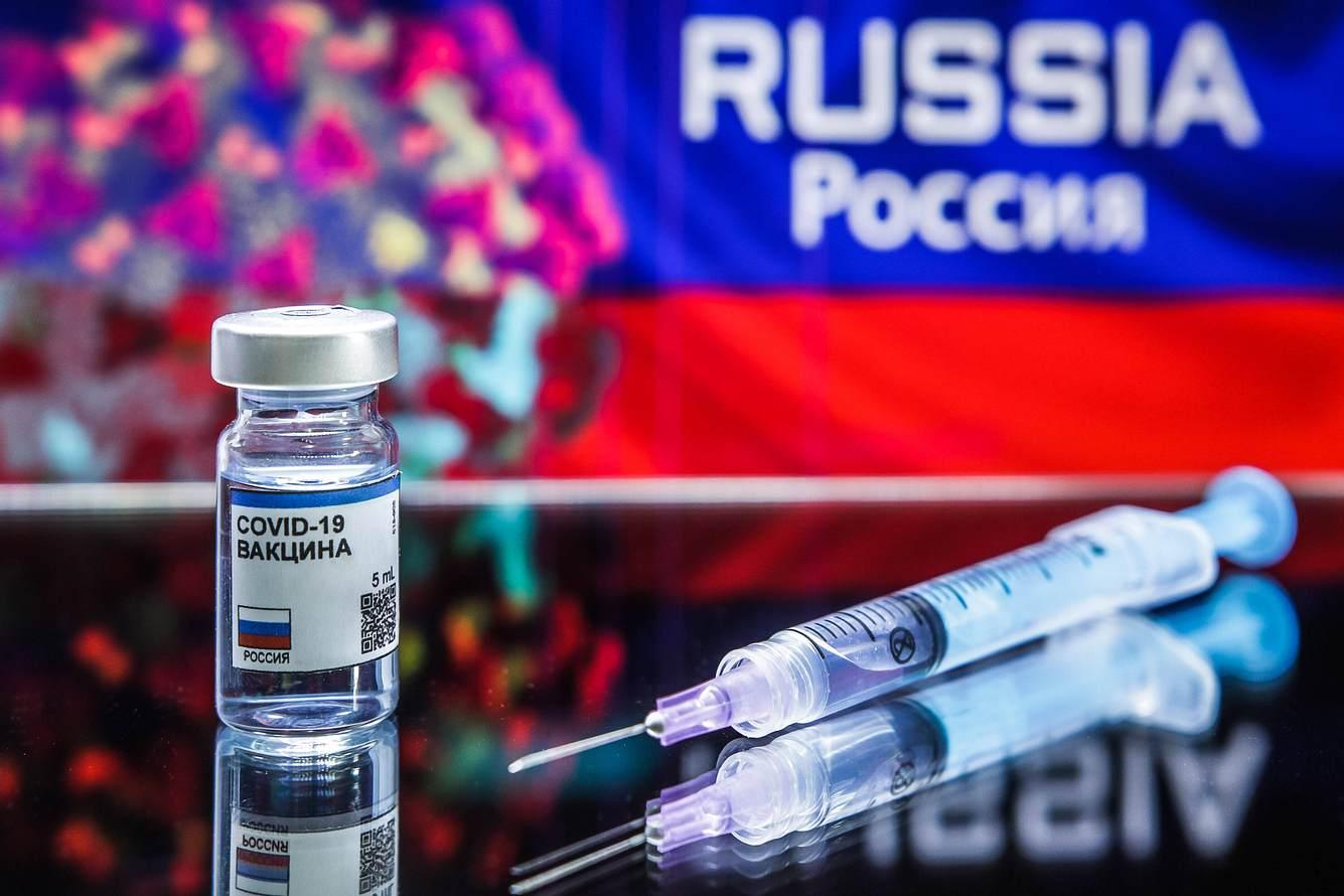 Glas mit Impfstoff und Spritze vor Russland-Flagge