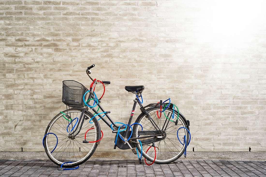 Ein Fahrrad steht mit vielen Fahradschlössern behängt an einer Wand