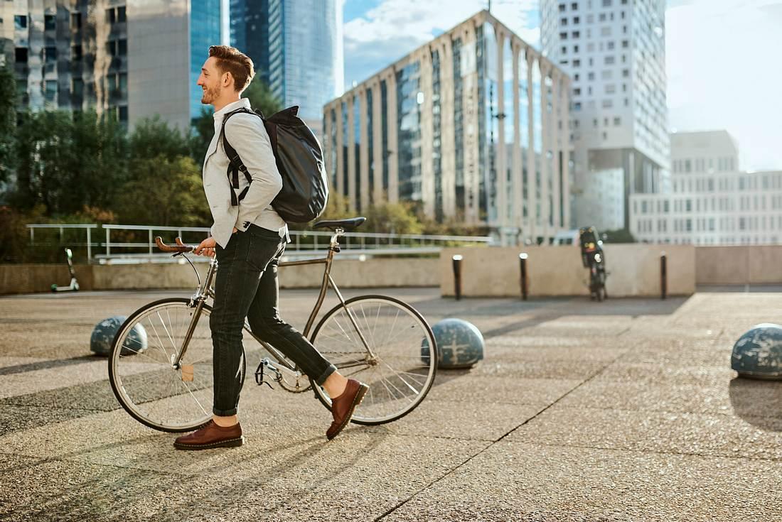 Ein Mann trägt seine Fahrradtasche als Rucksack, während er sein Rad schiebt