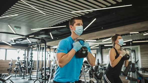 Mit Maske und Sicherheitsabstand im Fitnessstudio - Foto: iStock / svetikd