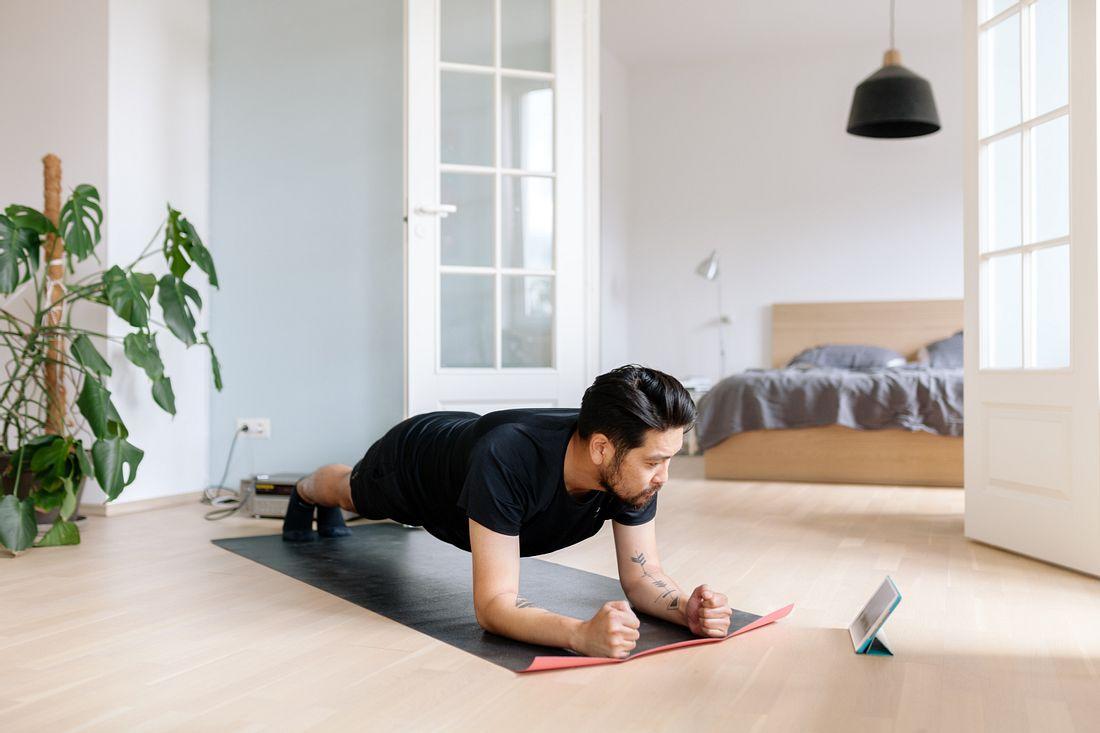 Mann macht einen Plank im Wohnzimmer