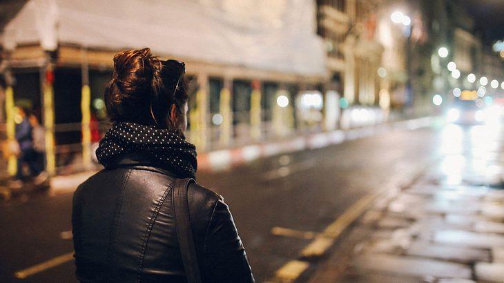 Frau allein auf dunkler Straße