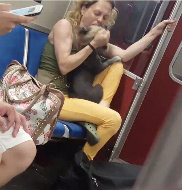 Tierquälerin? Eine Frau beißt ihren Hund in einer U-Bahn