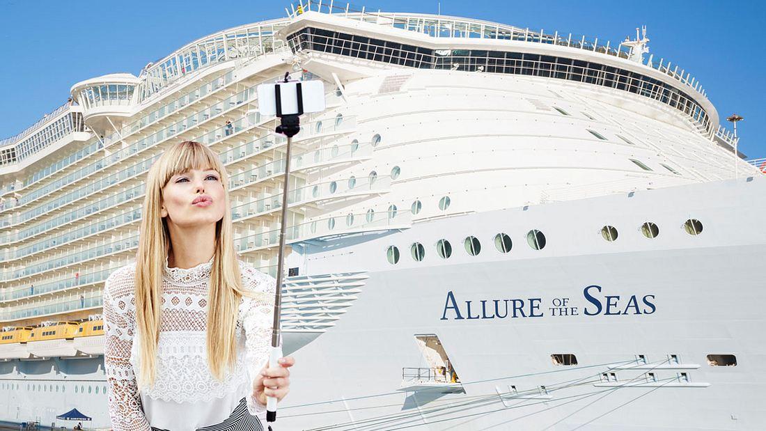 Frau macht Selfie vor Kreuzfahrtschiff