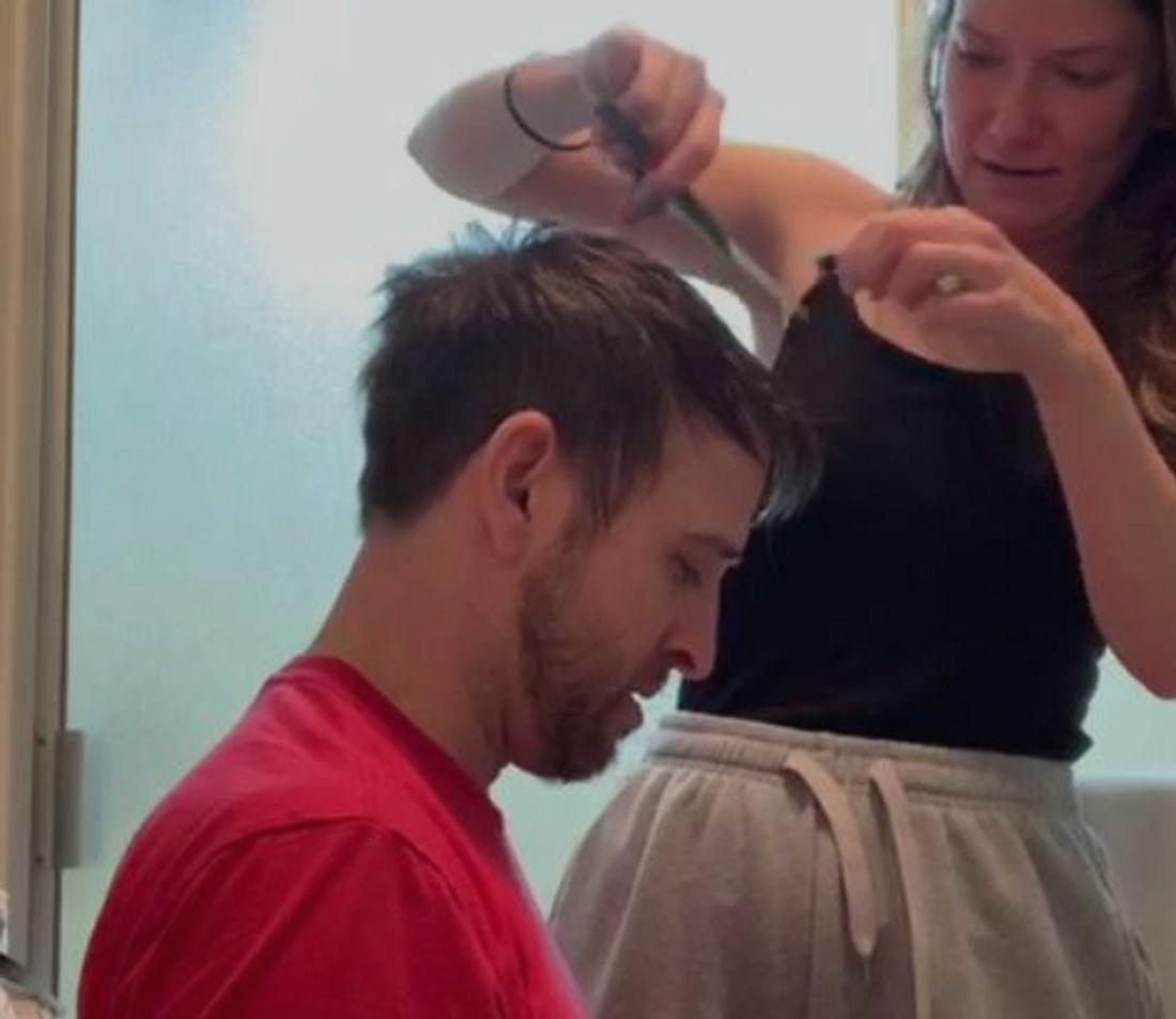 Frau schneidet ihrem Mann die Haare