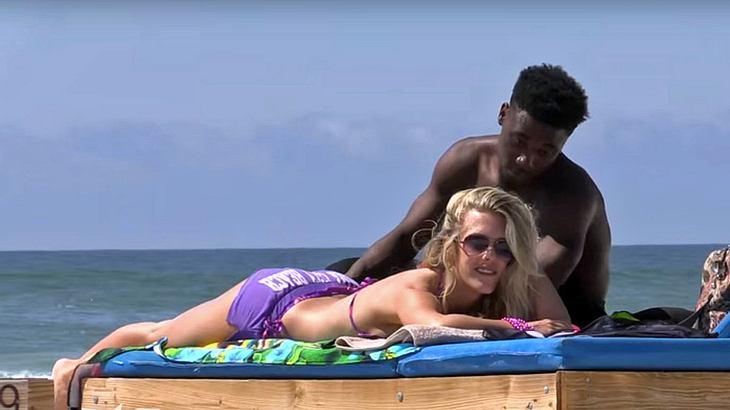 Ein Mann massiert eine attraktive Blondine am Strand. Dann erlebt er sein blaues Wunder