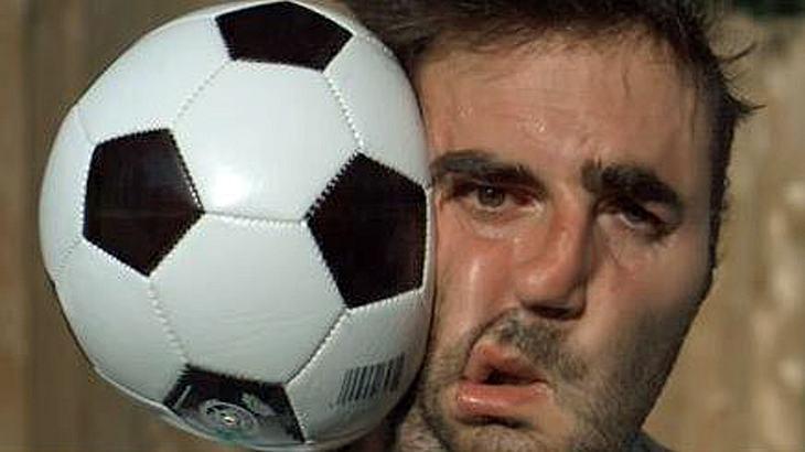 Ein Mann wird von einem Fußball im Gesicht getroffen