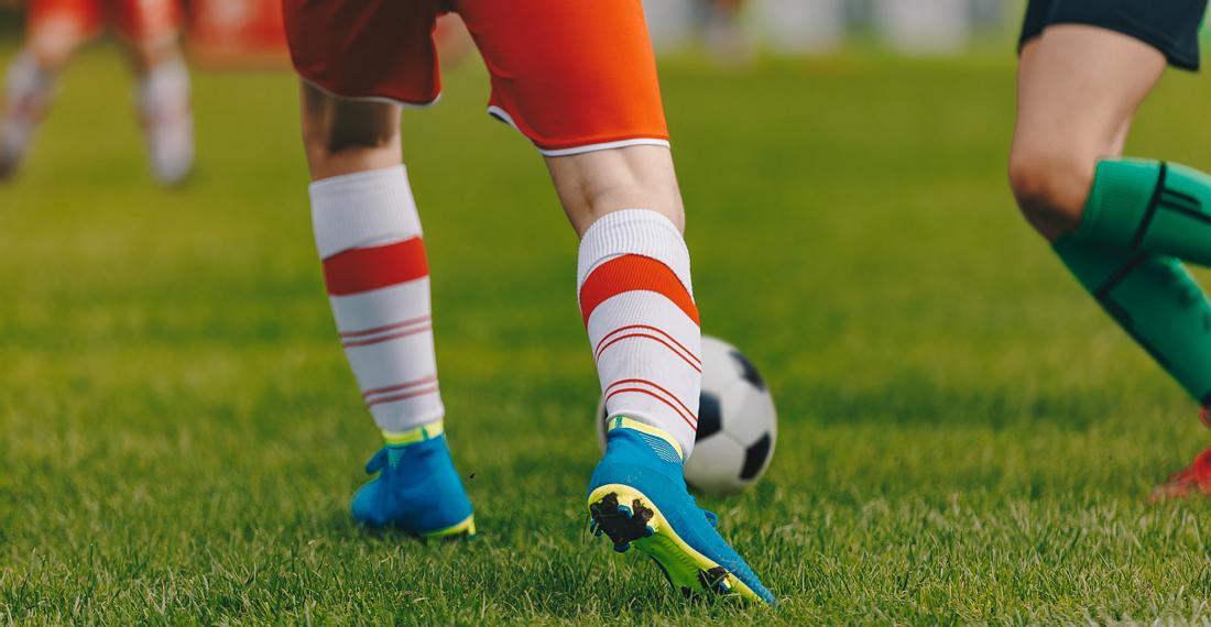 Ein Mann spielt Fußball in Fußballschuhen mit Socken